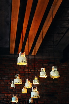 Many vintage lamps hanging under the ceiling in cafe