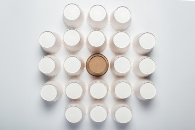 밝은 배경에 거꾸로 뒤집힌 많은 흰색과 갈색 종이컵