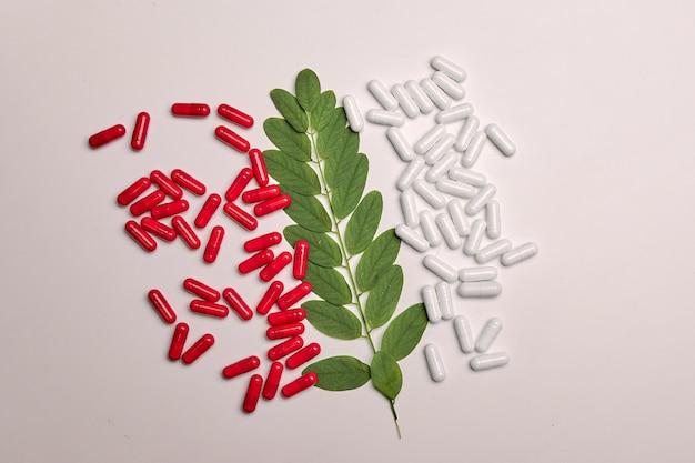 カラフルな背景の健康補助食品や薬の多くの白と赤のカプセル錠剤