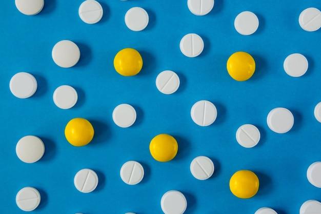 青の背景に多くの白と赤の錠剤