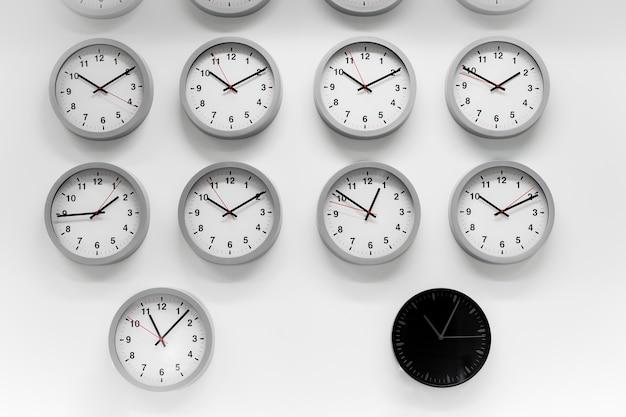 多くの白い時計と黒の古典的な丸い壁の時計。時間の異なる概念