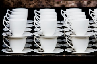 Many white coffee cups in a line over a buffet