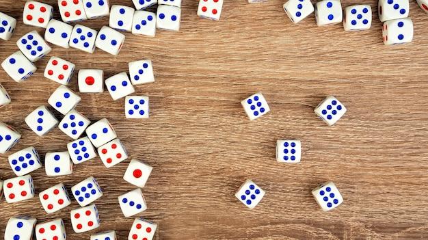 Многие белые кости с красными и синими точками на деревянном столе. концепция азартных игр казино. крупный план. в помещении.