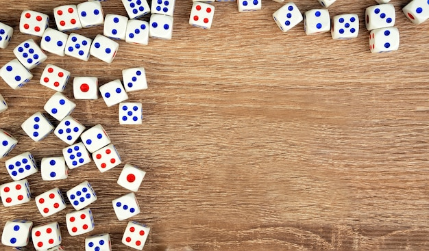 Многие белые кости с красными и синими точками на деревянном столе. концепция азартных игр казино.