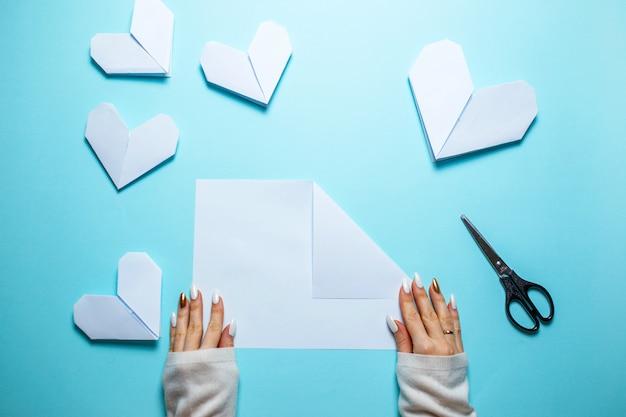 Много белых сердец origami на голубой предпосылке с листом бумаги и ножницами в центре. день святого валентина карты с женщиной, делая оригами сердце на синем фоне.