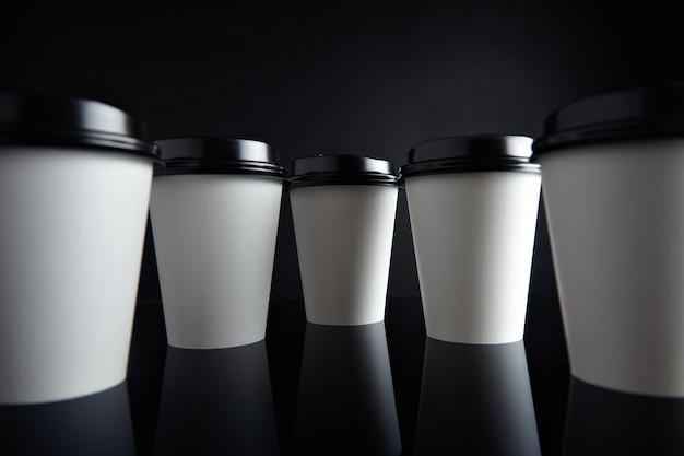 視差の視点で提示されたキャップで閉じられた熱い飲み物のための多くの白い持ち帰り用の紙コップ