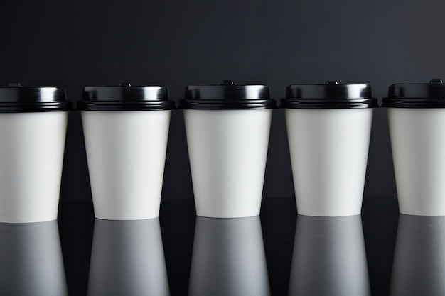 Many white take away paper cups for hot beverages closed with caps presented in line