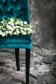 Many white tulips on a green chair on a gray background