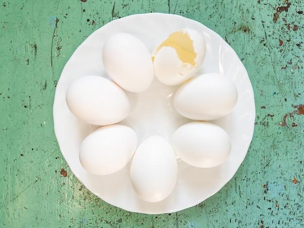 Множество целых белых яиц и одно разбитое яйцо лежат в кругу на белой тарелке на зеленом фоне.