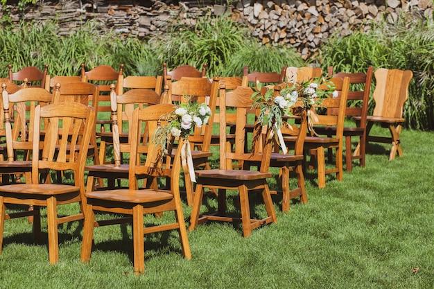 結婚式の花で飾られた多くの木製の椅子