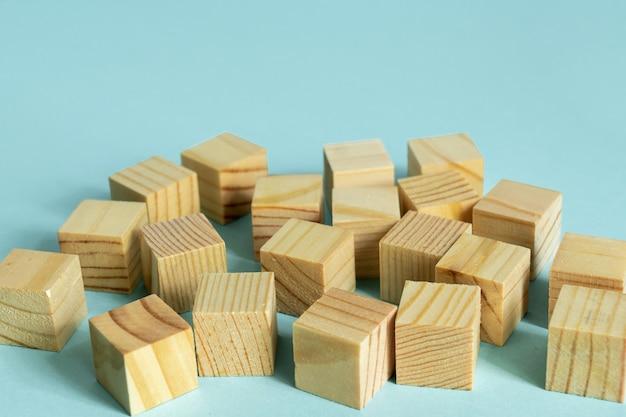青の背景に多くの木製キューブ。建設と開発のコンセプト。デザイナーのためのモックアップ。