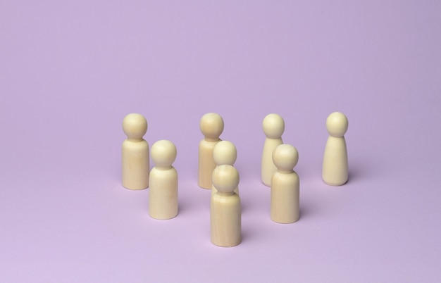 Many wooden figures of men stand on a lilac surface, the crowd at the rally Premium Photo