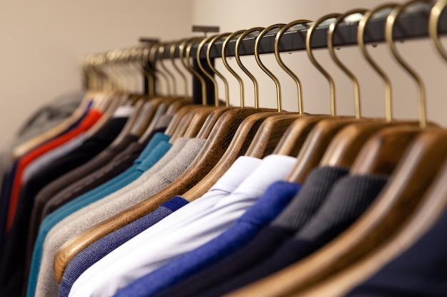 Many wooden hangers with different male clothes in boutique on metal stand.