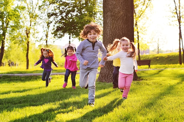 Many young children smiling running along the grass in the park. childhood.