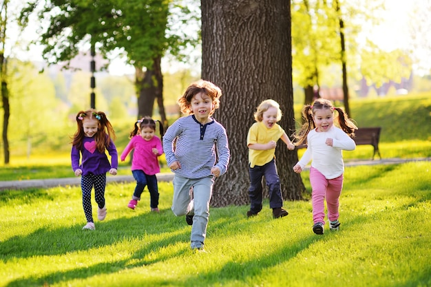 Many young children smiling running along the grass in the park. childhood