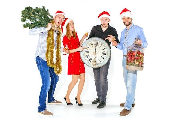Многие молодые женщины и мужчины пьют на рождественской вечеринке в студии.