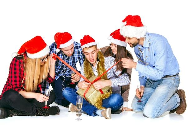 贈り物と白いスタジオの背景にクリスマスパーティーで飲む多くの若い女性と男性