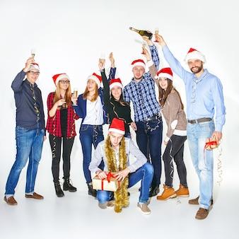 多くの若い女性と白いスタジオ背景のクリスマスパーティーで飲む男性