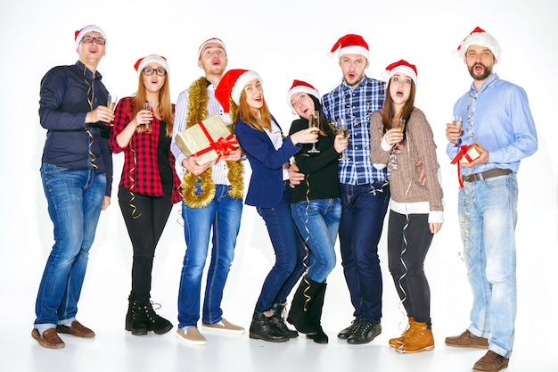 白いスタジオの背景にクリスマスパーティーで飲む多くの若い女性と男性