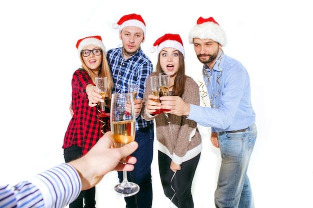 Многие молодые женщины и мужчины пьют на рождественской вечеринке на фоне белой студии