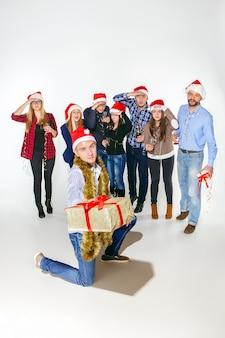 多くの若い女性と白いスタジオのクリスマスパーティーで飲む男性