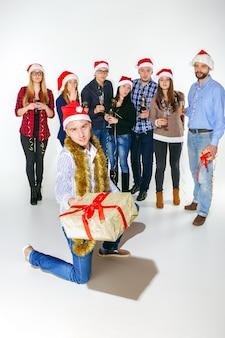 Molte giovani donne e uomini che bevono alla festa di natale su sfondo bianco studio