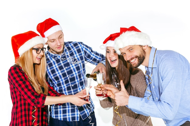 Many young women and men drinking at christmas party on white studio