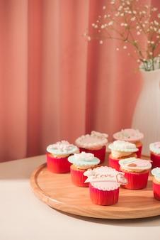 多くのおいしいカップケーキ。明るい背景の上のテーブル上のバレンタインの甘い愛のカップケーキ