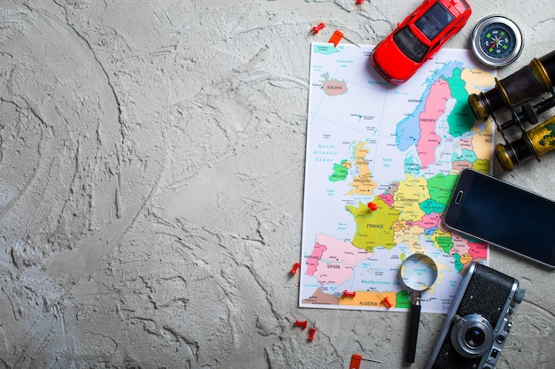 The map, airplane, and traveling stuff on a wooden table