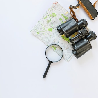 Map; binoculars and magnifying glass on white surface