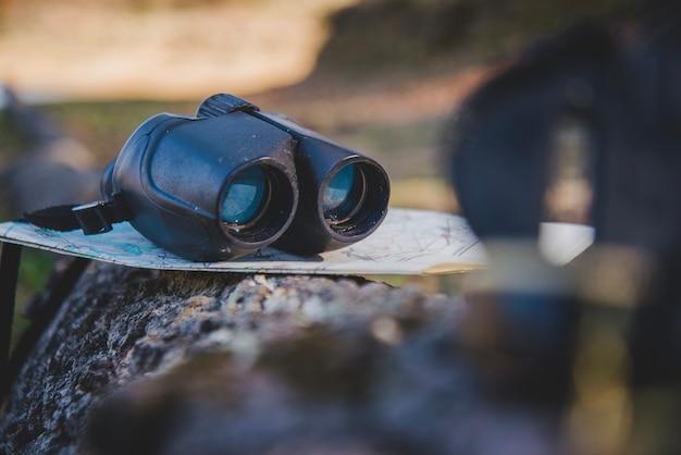 Map and binoculars on a fallen log