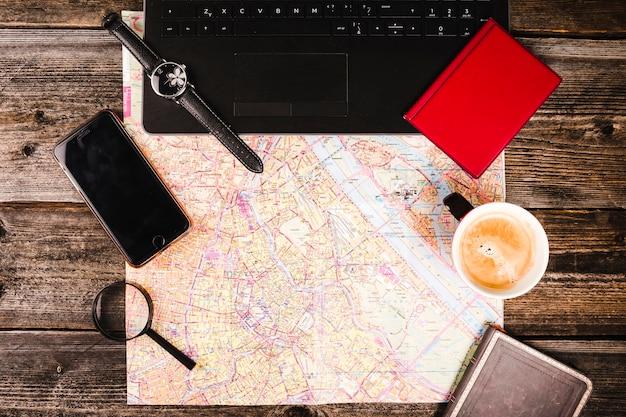 地図、コーヒー、電子機器、アクセサリー、木製テーブル
