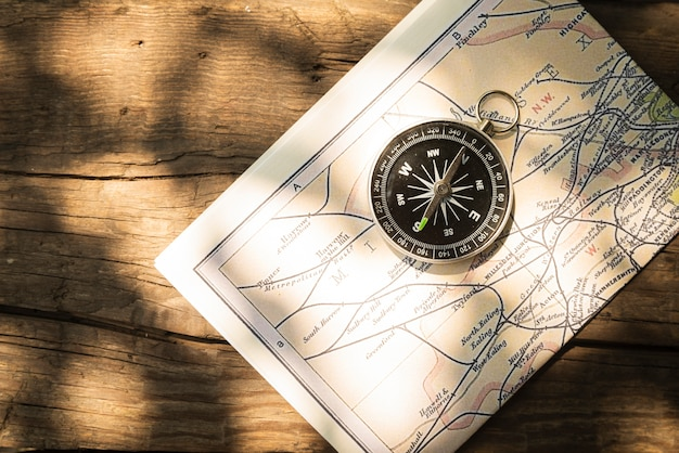 Map and compass with wooden background