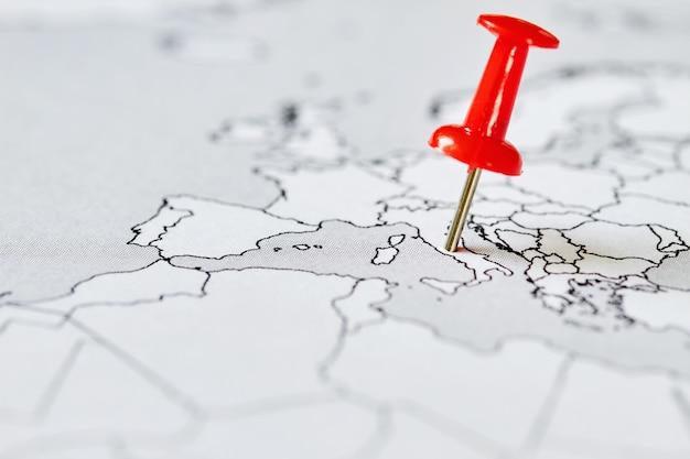 Карта европы с красной канцелярской кнопкой, на которой отмечена италия, где эпидемия ковид-19. понятие о распространении вируса. крупный план