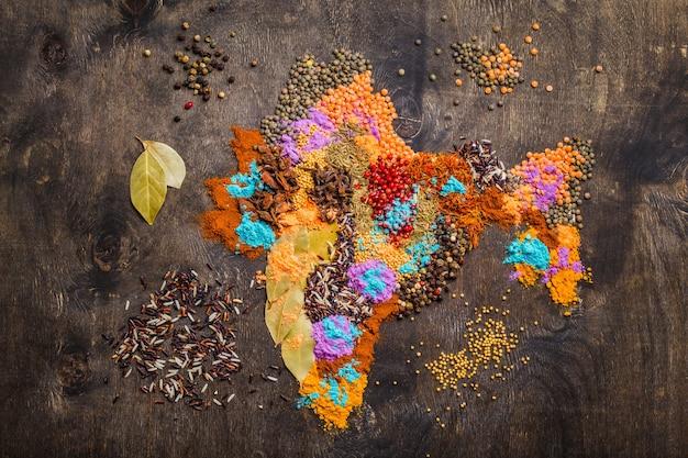 暗い木製の背景、上面図にさまざまな伝統的なインドのスパイス、米、レンズ豆、ホーリー色の粉末から作られたインドの地図。インド料理を調理するための調味料と材料、コンセプト