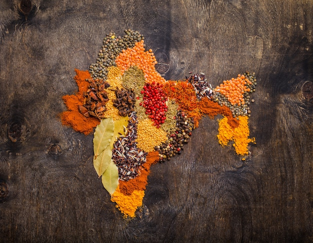さまざまな伝統的なインドのスパイス、米、暗い木製の背景にレンズ豆から作られたインドの地図、上面図。インド料理を調理するための調味料と材料、コンセプト