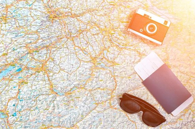 ヴィンテージカメラ、パスポート、サングラスを備えた道路の地図。上からの眺め。旅行の概念。スペースをコピーします。フラットレイ。太陽フレア