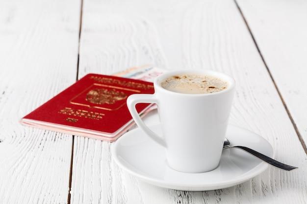 地図、パスポート、ノートブック、木製テーブルの上のコーヒーカップ、旅行のアイデア