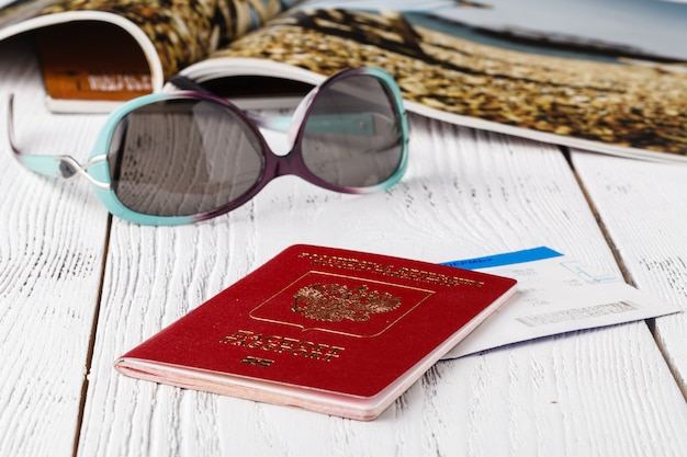 Map, passport, notebook and cup of coffee on wooden table, travel ideas