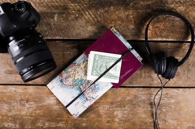 Map with passport, banknotes, headphone and dslr camera on wooden surface