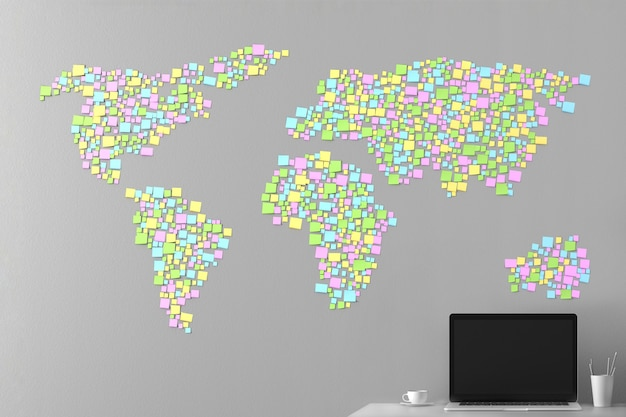 Map of the world from the stickers pasted on the wall with a laptop standing next
