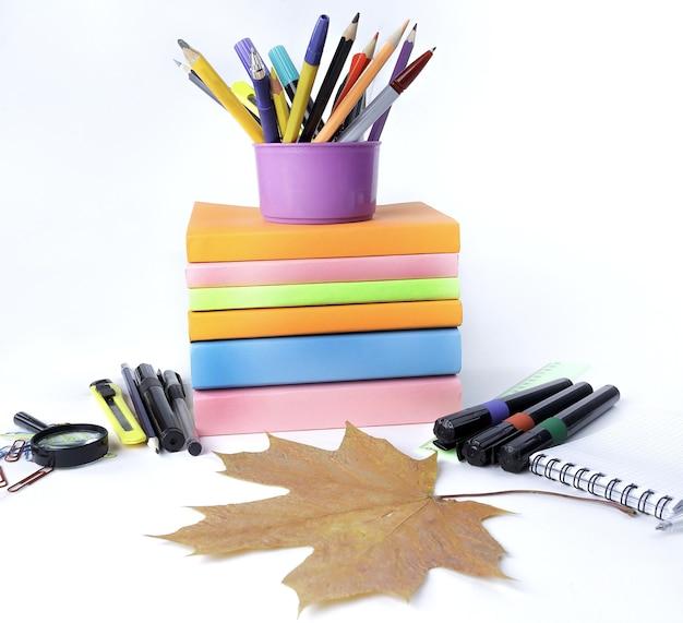 Кленовый лист и школьные принадлежности на белом фоне