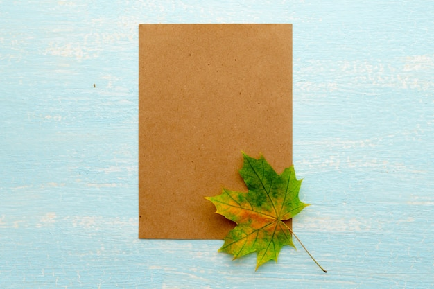 A maple leaf near a blank sheet of paper. frame for text, autumn theme. view from above.