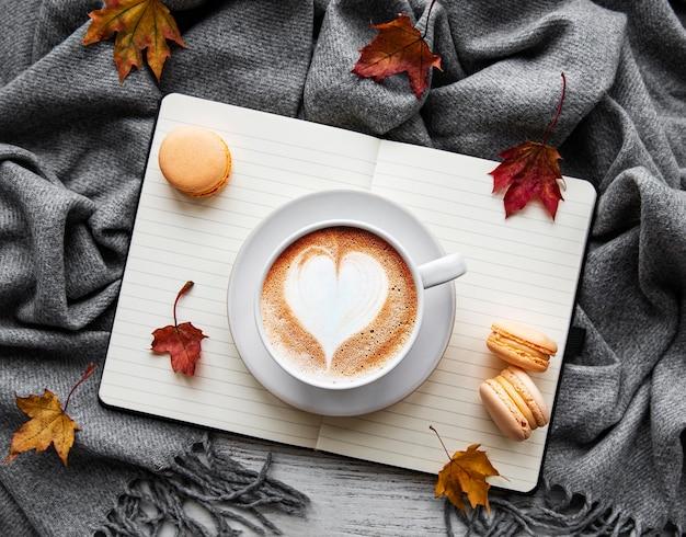 Кленовые листья, блокнот, кофейная чашка и шарф. осенняя или зимняя концепция.