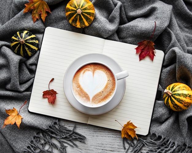 Кленовые листья, блокнот, кофейная чашка и шарф.