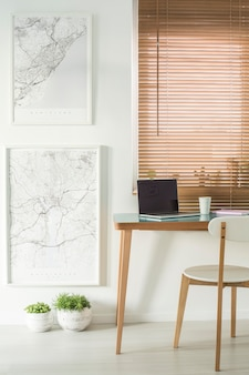 Maps on the wall next to a desk with a laptop and chair standing by the window with blinds workspace