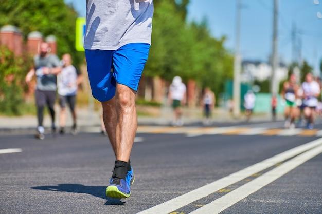 都市道路のマラソンランナー。ランニング競技。屋外での全力疾走。健康的なライフスタイル、フィットネススポーツイベント。