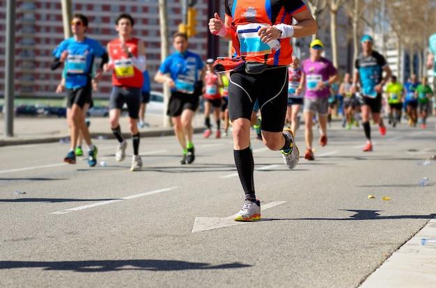 マラソンランニングレース、ロードレース、スポーツ競技、フィットネス、健康的なライフスタイルコンセプトに多くのランナーの足