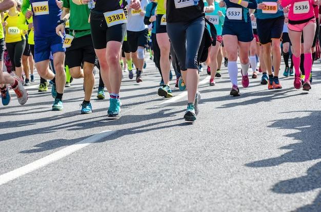 Марафонский бег, многие бегуны, ноги на шоссейных спортивных соревнованиях