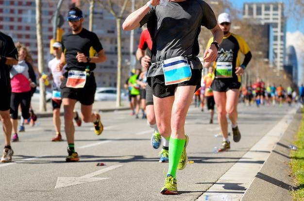 Марафонская гонка, много бегунов, ноги на дорожных гонках